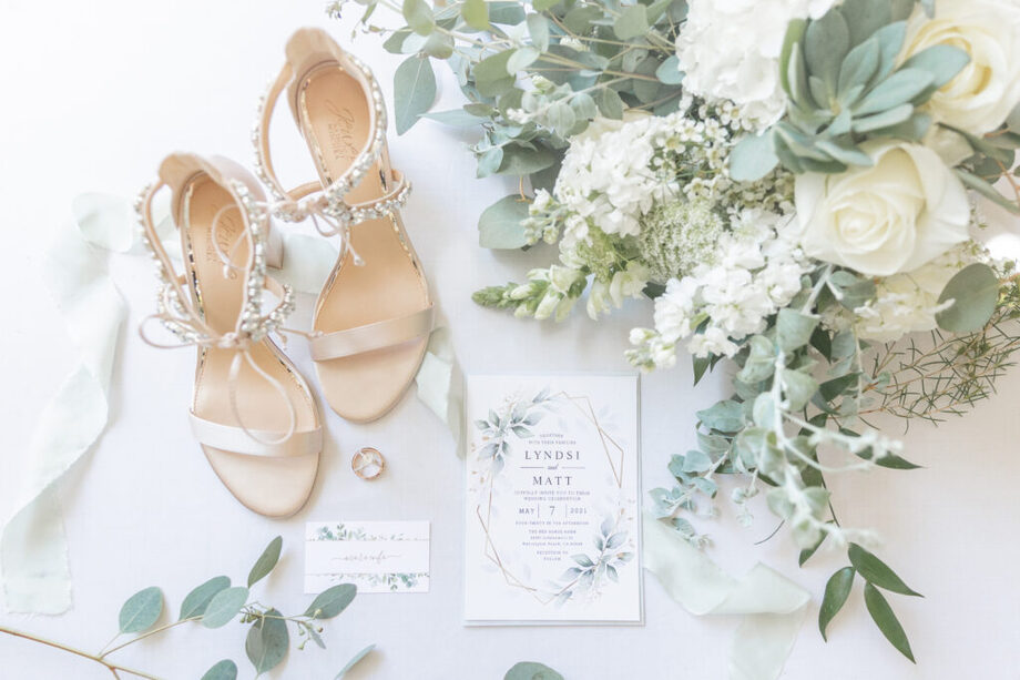 Wedding bouquet next to bouquet singles from wedding florist next to white wedding heels and a gorgeous floral wedding invitation