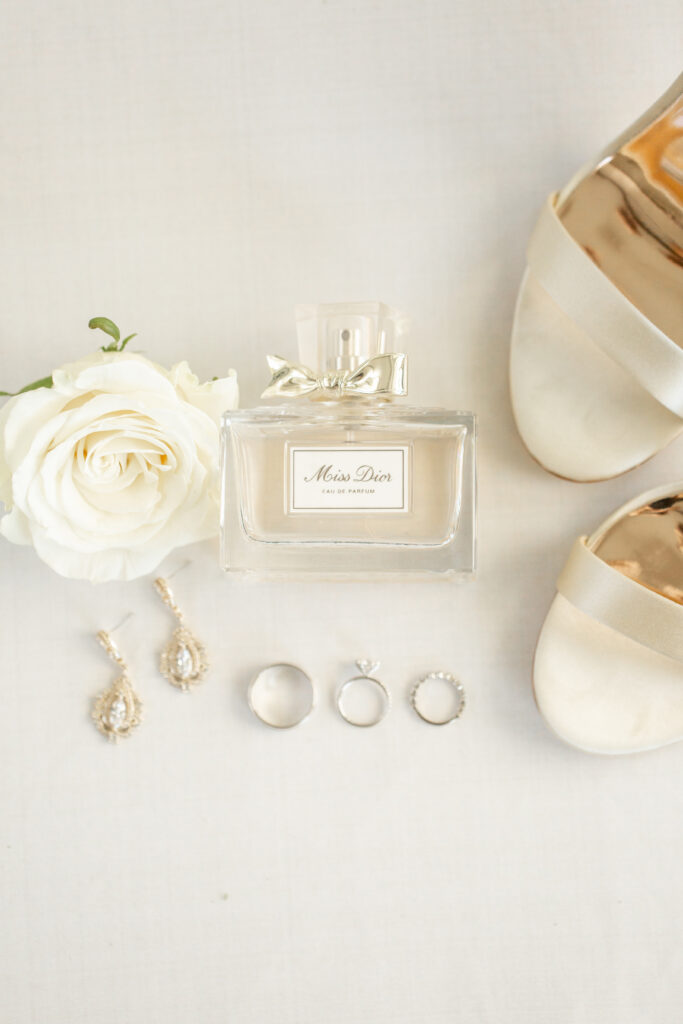 White rose from wedding bouquet next to wedding jewelry and white wedding heels